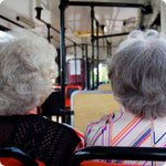 Two older ladies sitting on a bus.