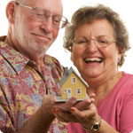 Man and woman with a model house in their hands.
