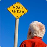 "A older man looks at a sign which reads ""Road Ahead""."