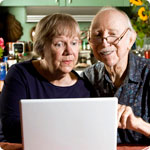 An older man and woman search for information on the internet.