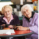Two older ladies in a cafe.